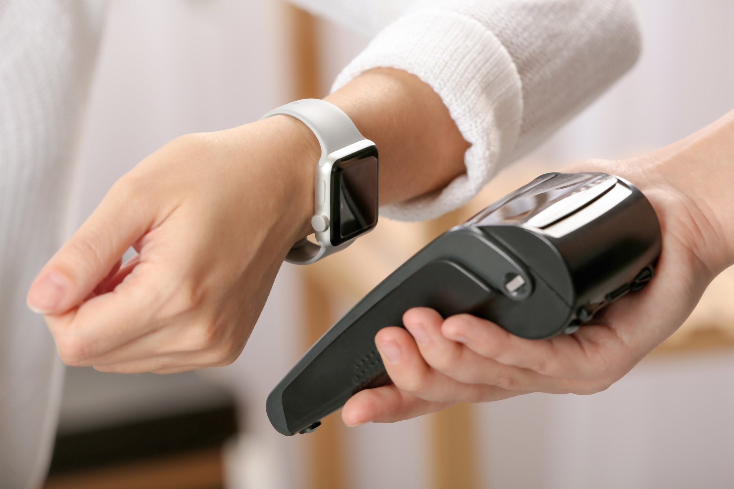 : A customer making a contactless purchase through her smartwatch.